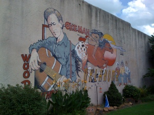 Woody Guthrie has a mural.  Woody Guthrie has a folk festival.  Do YOU have a mural or a folk festival?